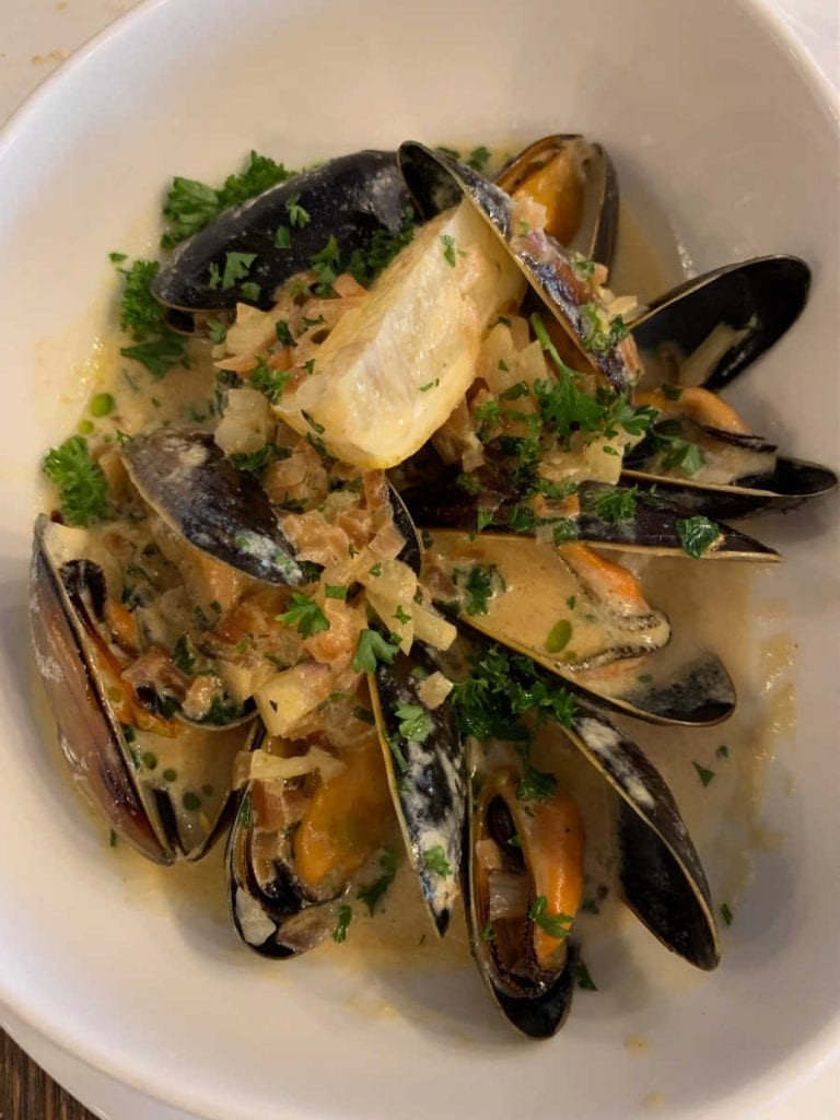 mussels with a lemon wedge in a white bowl