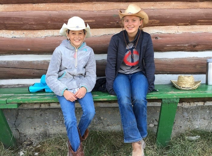 Genevieve and Hannah on bench with cowboy hats