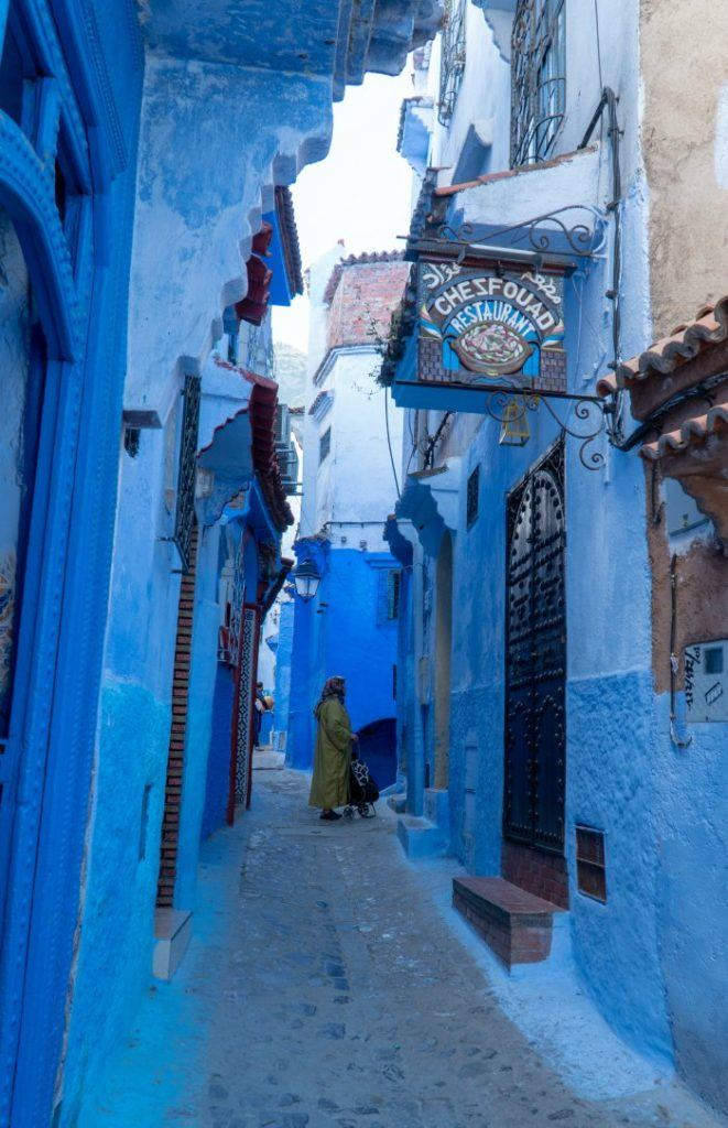 Women in blue street with Chezfouad Restaurant sign