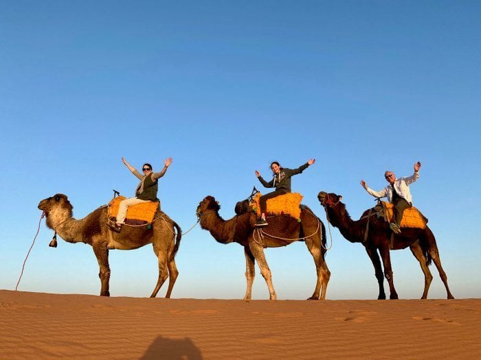 Riders on camels with hands up in the air