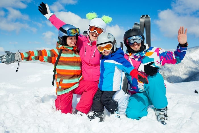 Family with mom, dad, and two kids kneeling in the snow on a ski resort smiling with arms out