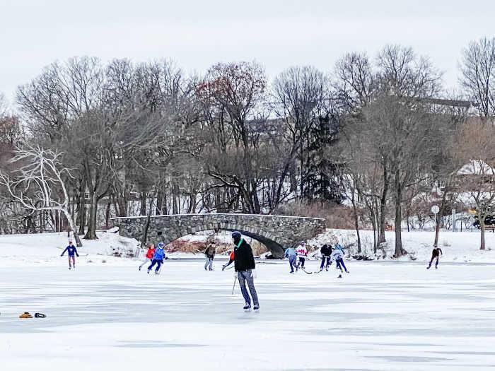 kids playing ice hockey on a lake