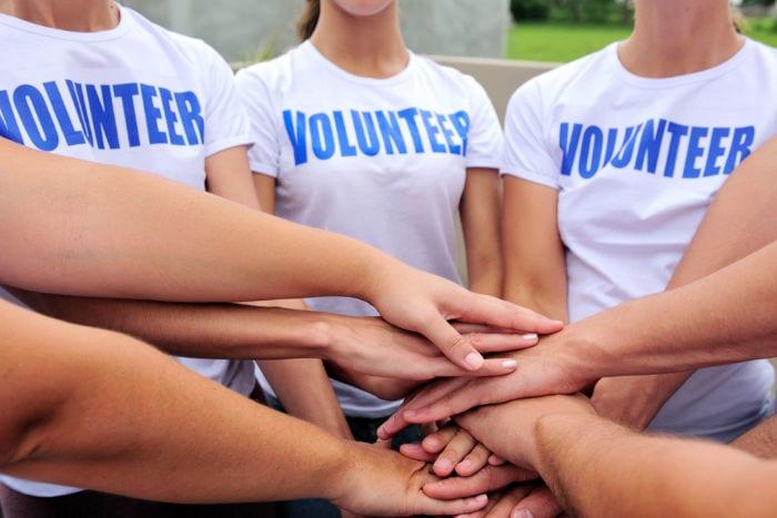 teen volunteers stacking hands