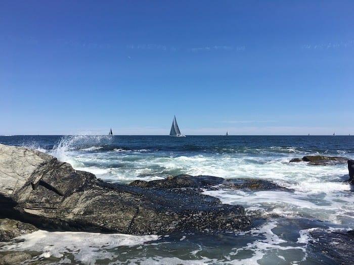 waves crashing on rocks and sailboat at Beavertail state park