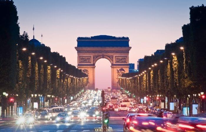 Traffic lights going through the Arc de Triomphe in Paris at dusk