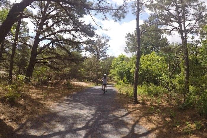 girl biking on path through the woods