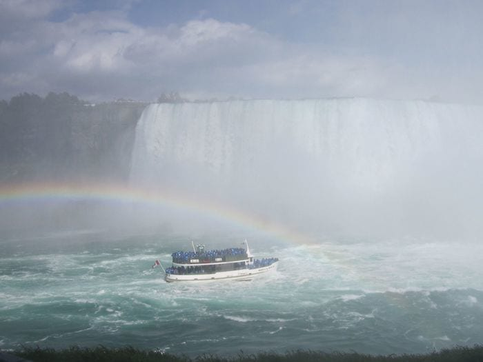 Maid of the Mist boat under rainbow approaching Niagara Falls
