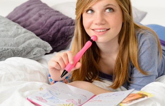 teen girl writing in journal