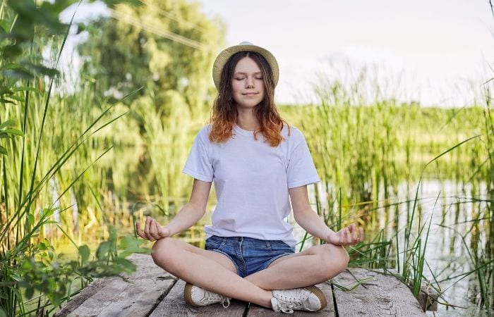 teen meditating on dock near grass and water