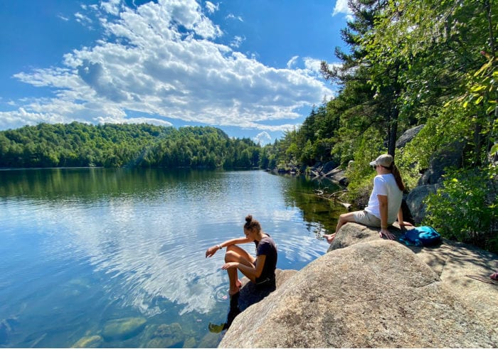 Girl and mom sitting on the rocks by Copperas Pond