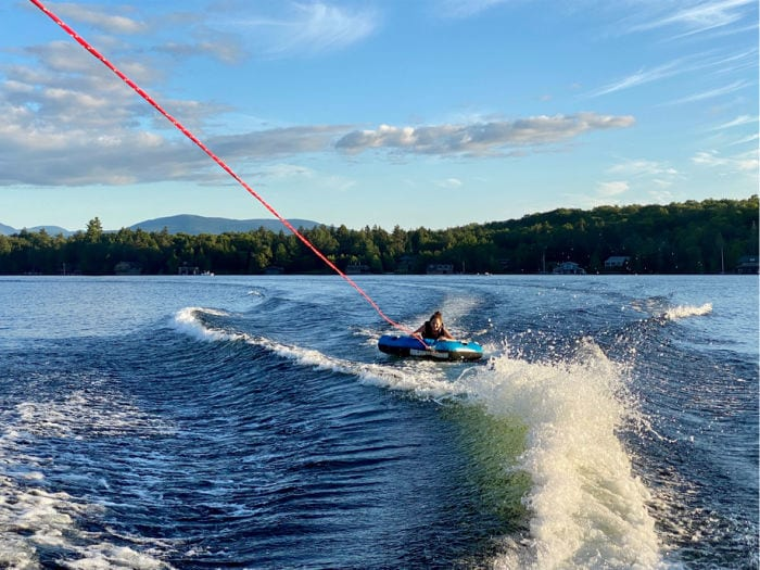 girl being pulled behind a boat on a tube on Lake Placid