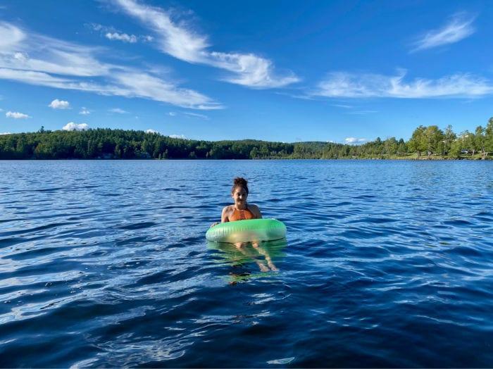 girl in tube swimming in Lake Colby