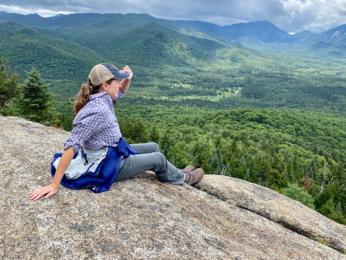 Female hiker sitting and holding hat on top of Mt Von Hovenberg