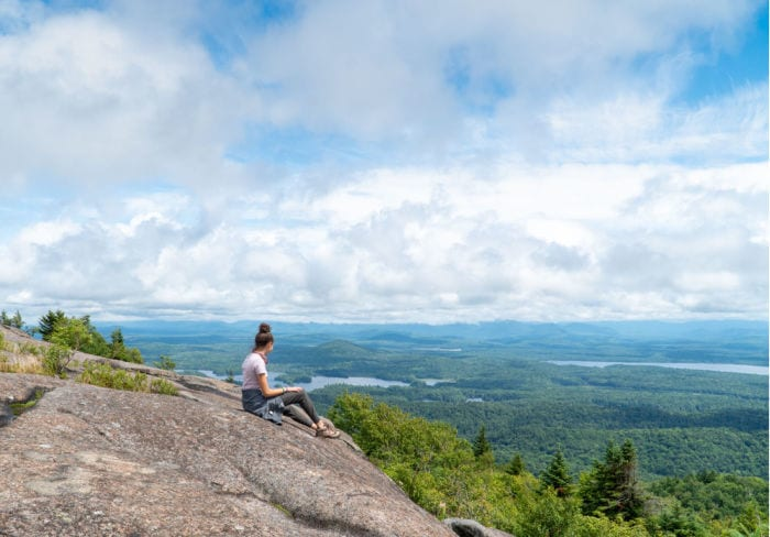 Girl looking out at view at the summit of St Regis Mountain in the Adirondacks