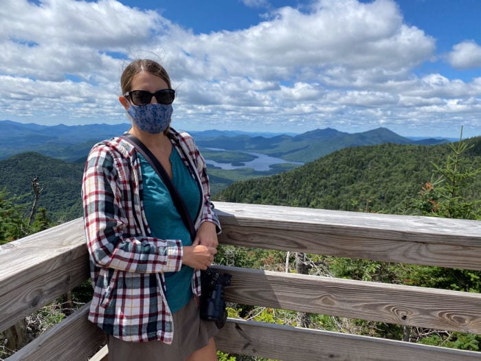 woman wearing face mask with view of Lake Placid in background from top of Little Whiteface Mountain