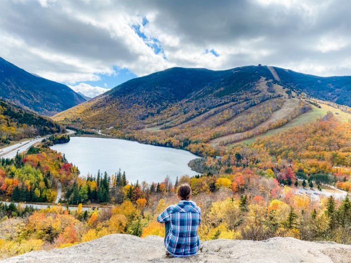 Woman sitting on Artists Bluff in NH overlooking Echo Lake with fall foliage on the trees and mountains