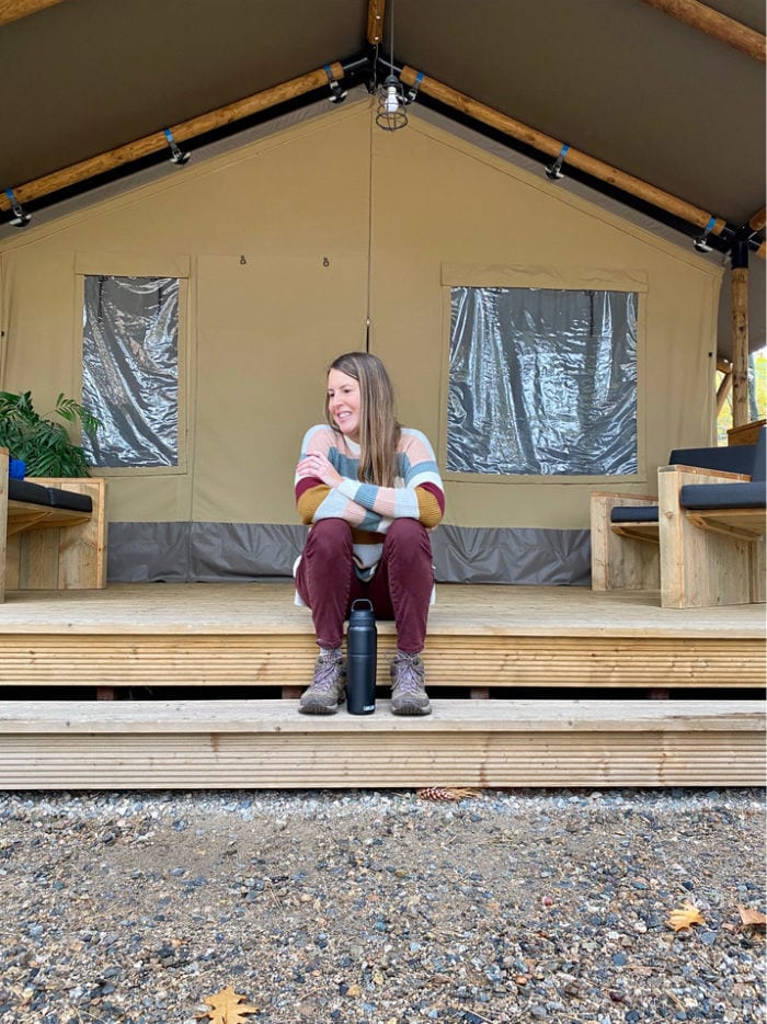 Woman in striped sweater sitting on porch steps of glamping tent
