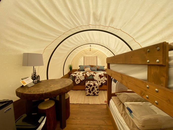 Bed, bunkbeds and table inside Conestoga glamping wagon