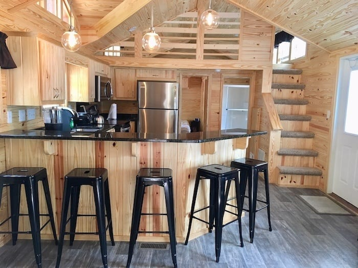 Normandy Farms deluxe cabin kitchen counter with stools and stairs to loft.