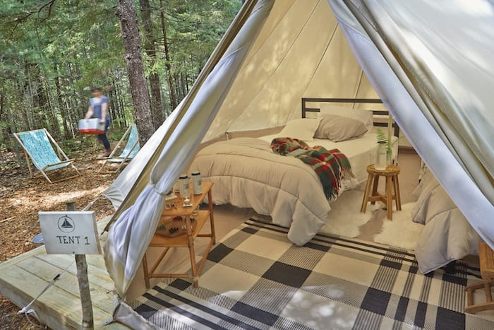 glamping tent inside showing bed and plaid rug from Tops'l Farm
