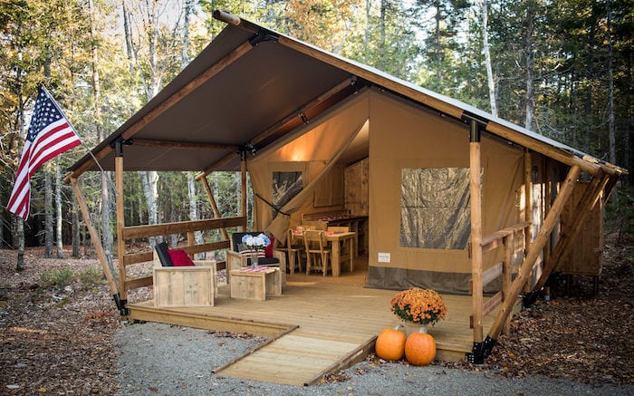Luxury glamping tent at Woods of Eden with American flag and pumpkins in front