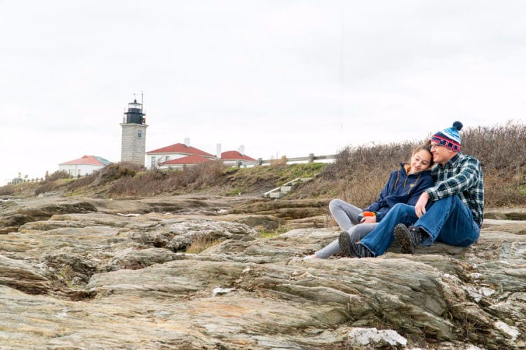 Dad and daughter sitting on rocks in front of Beavertail Lighthouse in Rhode Island