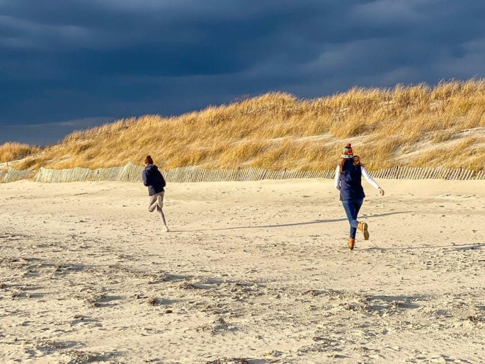 Mom and daughter running on the beach with dunes and dark blue sky in the background