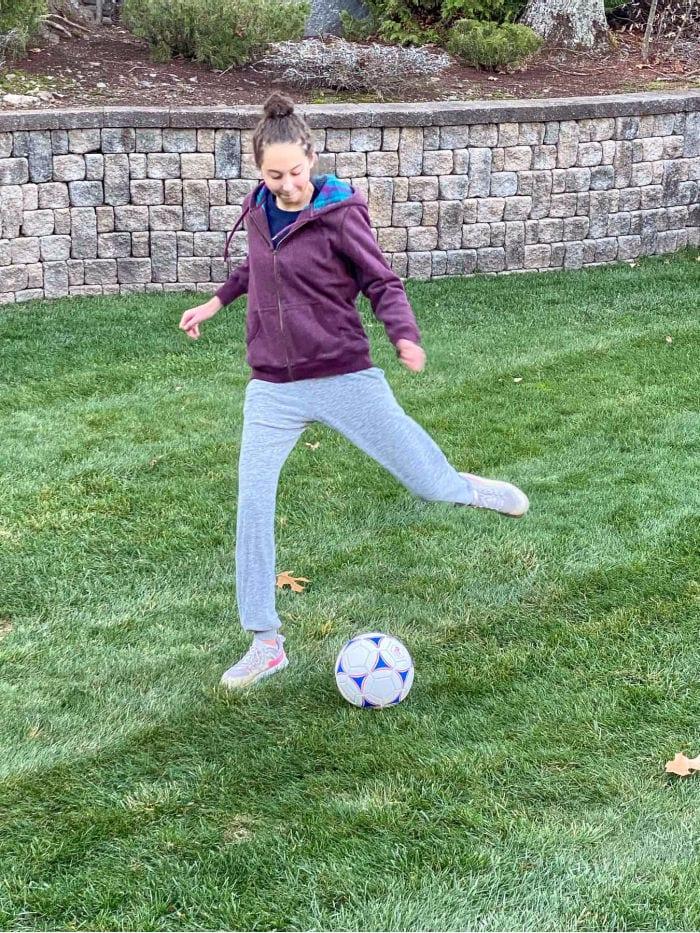Teen girl kicking soccer ball in backyard