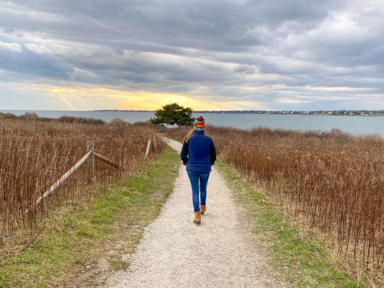 Woman walking on path with ocean in the distance at Sachuest wildlife refuge