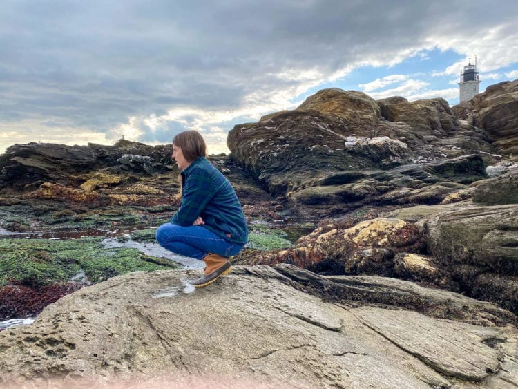 Woman in plaid flannel shirt crouching on rocks with Beavertail light house in the background