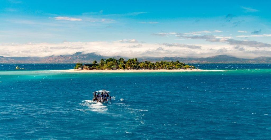 Fijian island with a boat approaching (from Canva)