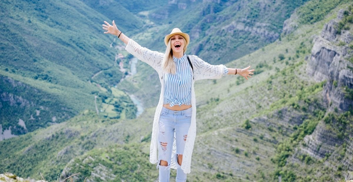 Teen girl in ripped jeans and a white sweater and hat with arms up in front of a valley