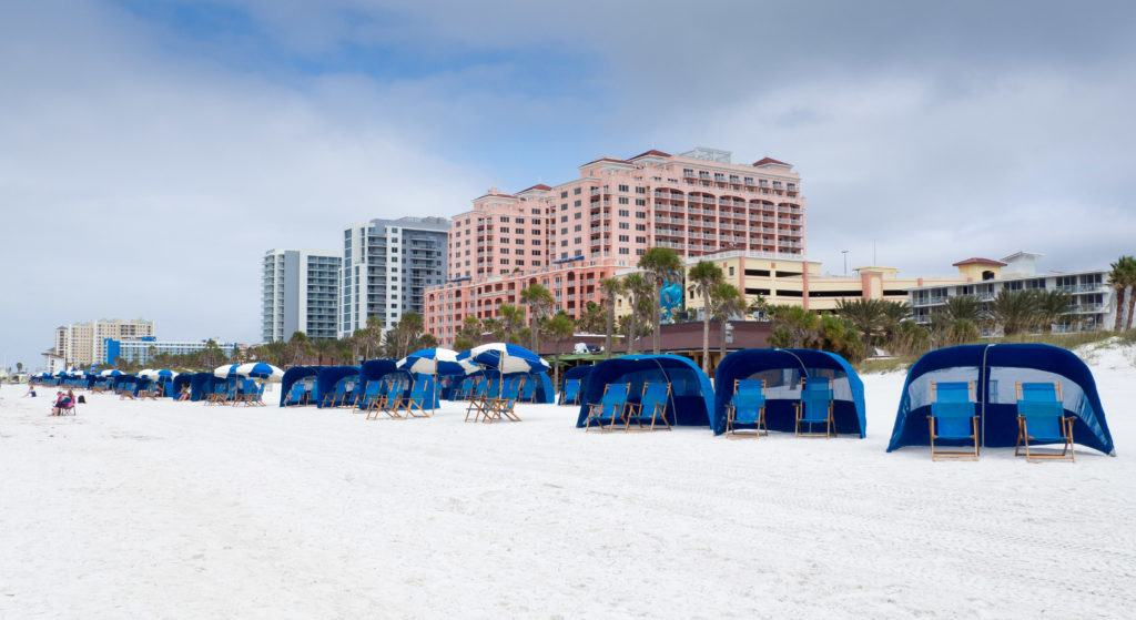 Blue beach cabanas in front of the pink Hyatt Regency Clearwater Beach