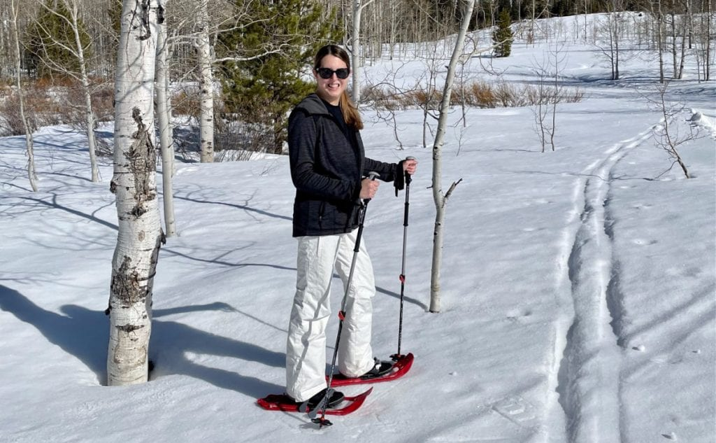 Woman in black jacket and white snow pants on snow shoes in the snow