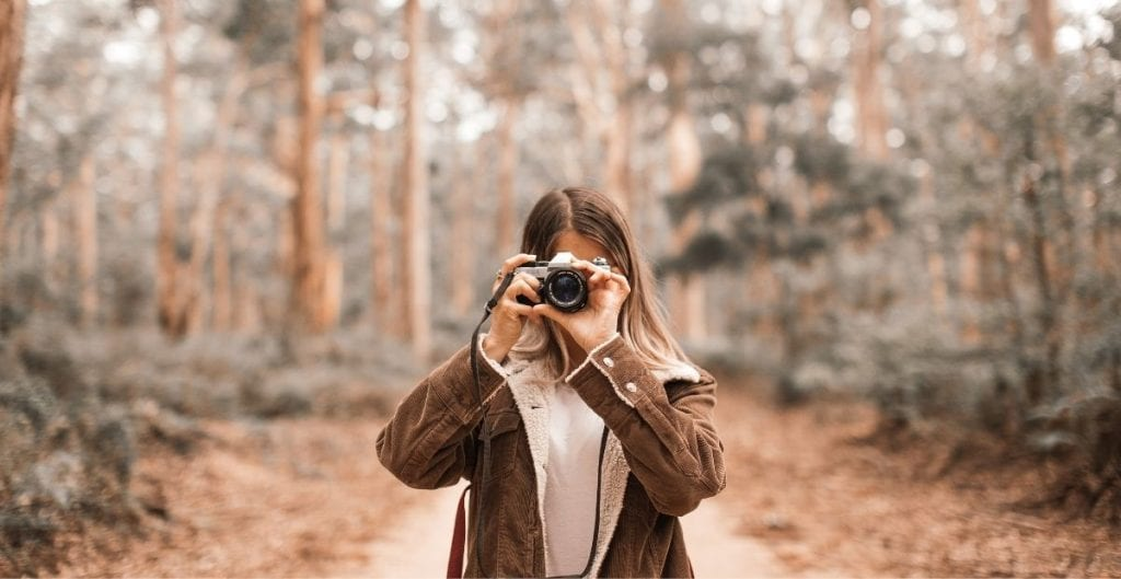 Woman in woods holding camera in front of her face from Canva