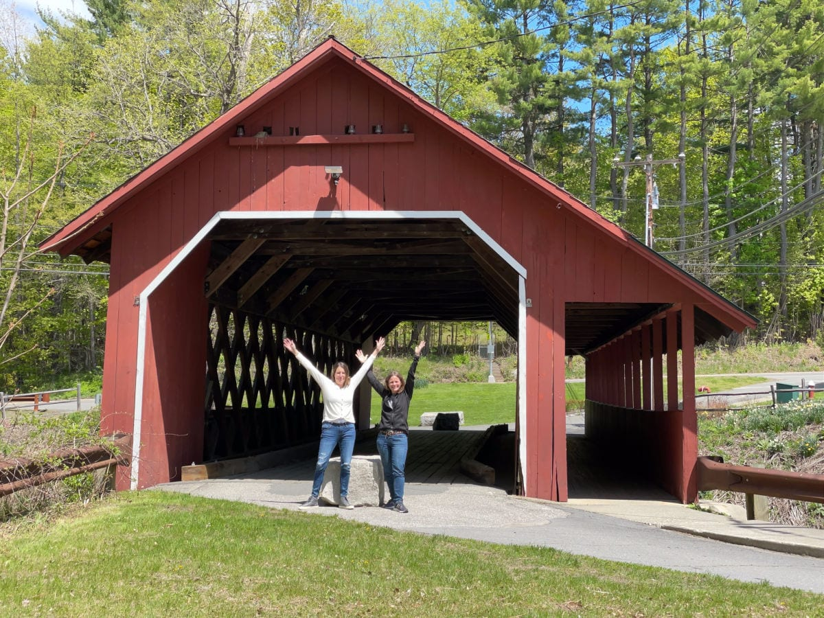 two women with their arms up standing at the entrance to a red covered bridge