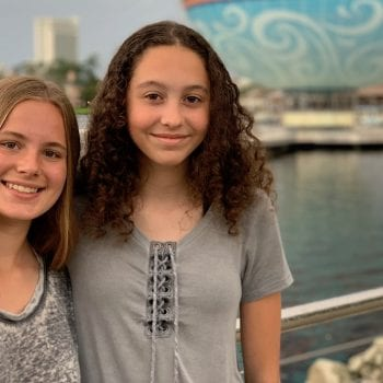 Two teen girls posing in front of the hot air balloon in Disney springs