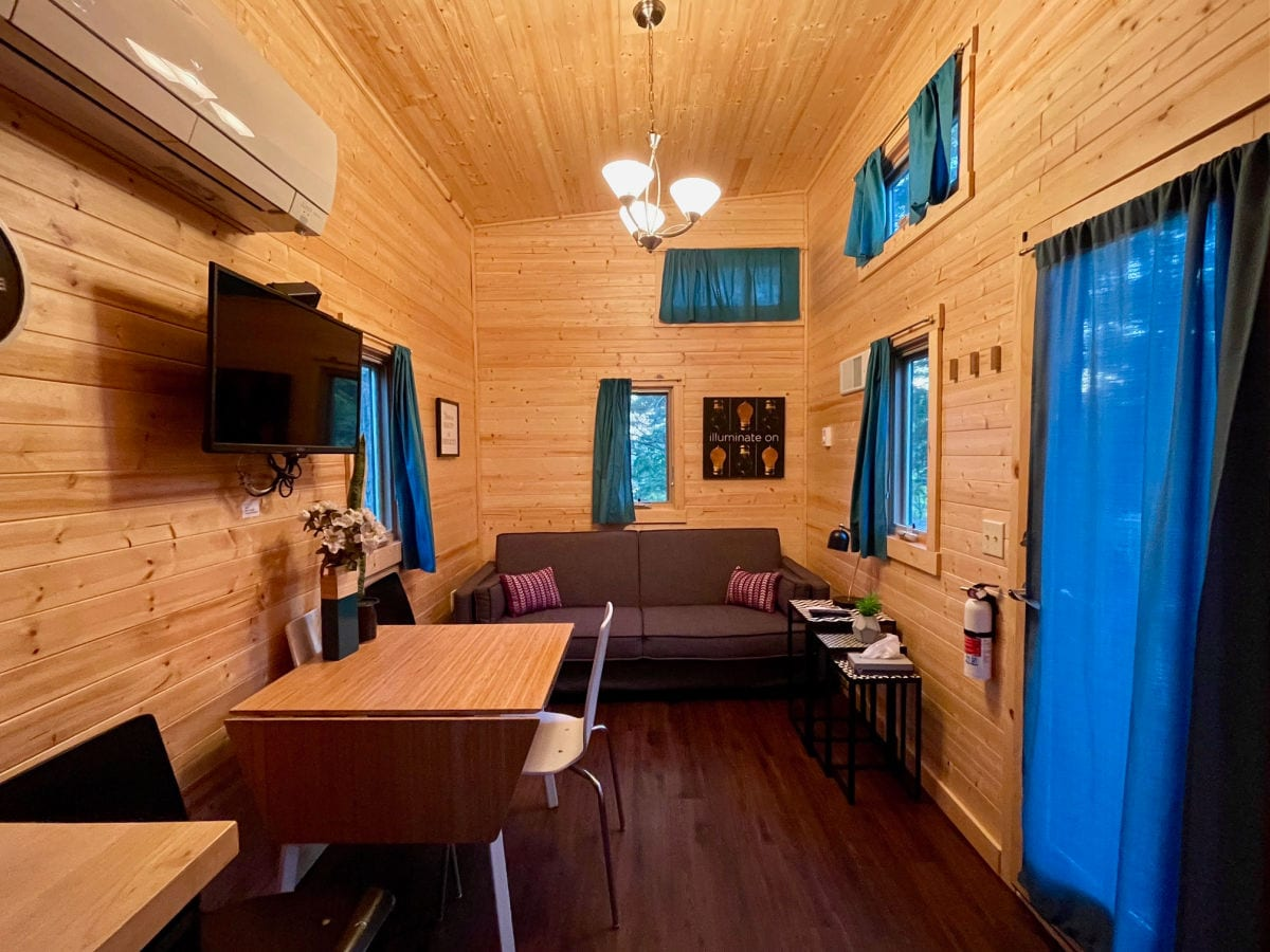 Emerson tiny house living room with sofa and kitchen table and chairs with wood walls and blue curtains