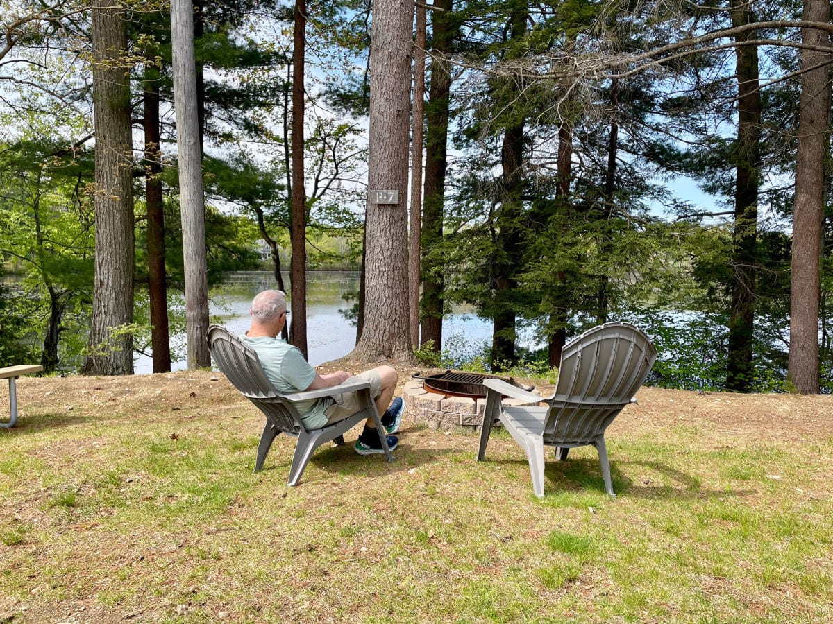 Man sitting in gray Adirondack chair in front of firing overlooking water with pine trees in front