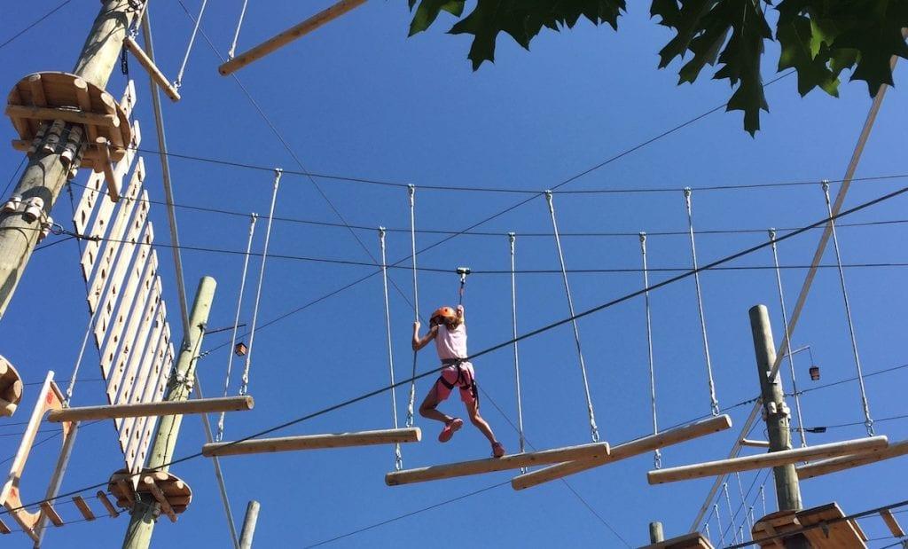 girl climbing on logs on tree top adventure course