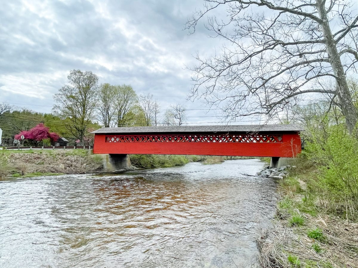Red covered bridge over a river from the side view