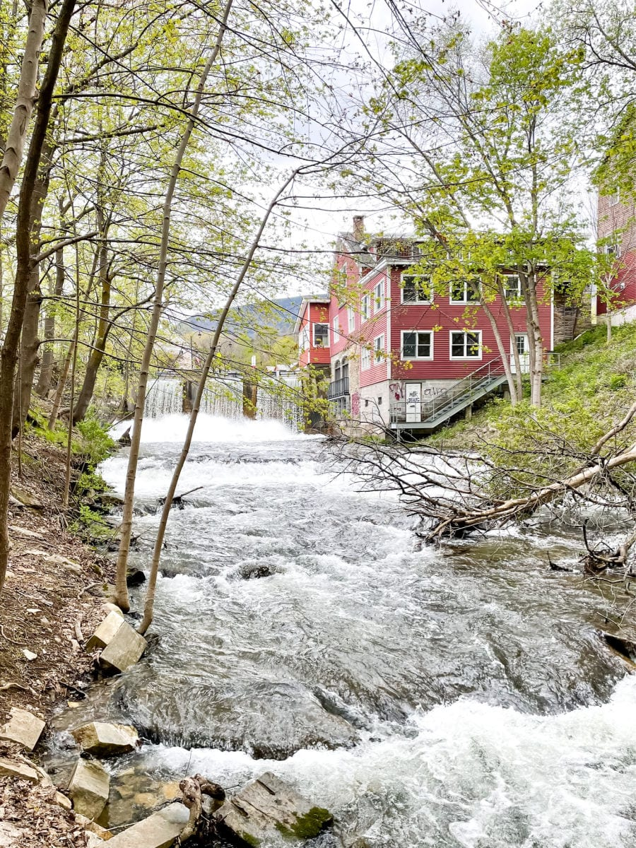 Waterfall and river next to red mill building in downtown Manchester Vermont