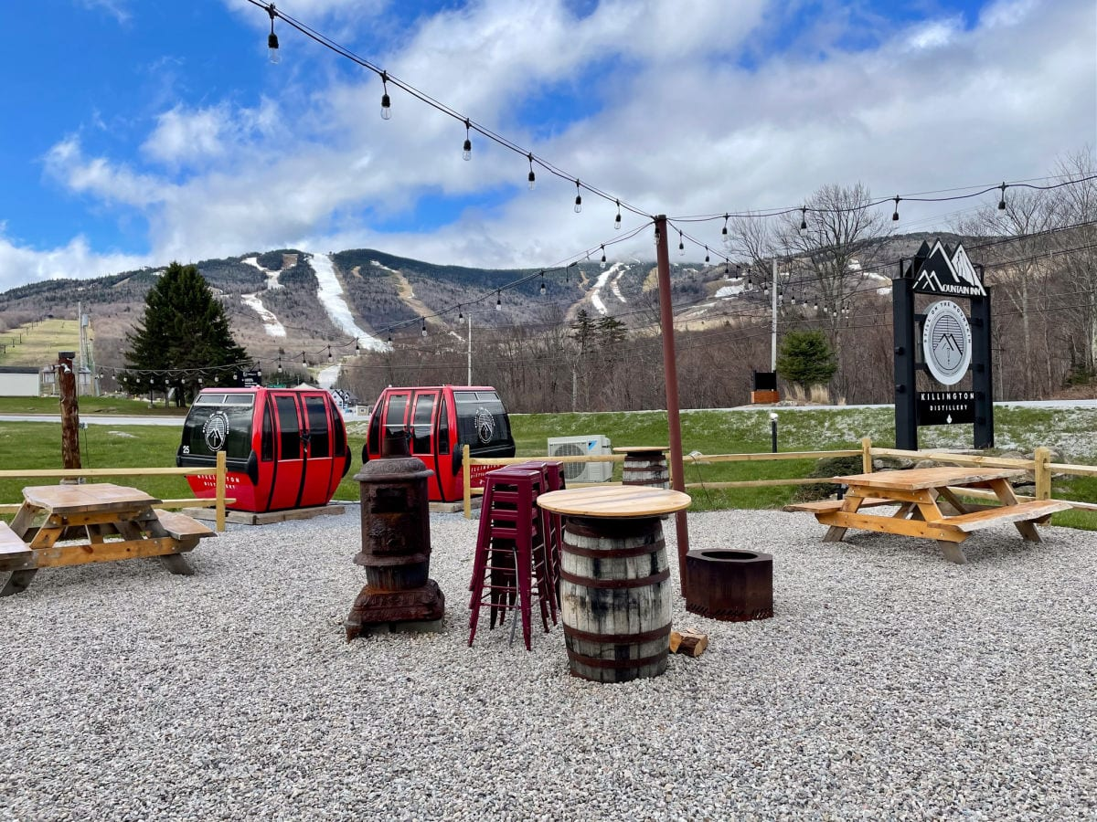 Mountain Inn sign and outdoor patio with two red gondolas, picnic tables and a view of the ski runs on Killington