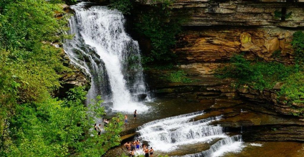 Cummins Falls waterfall with people swimming (Canva)