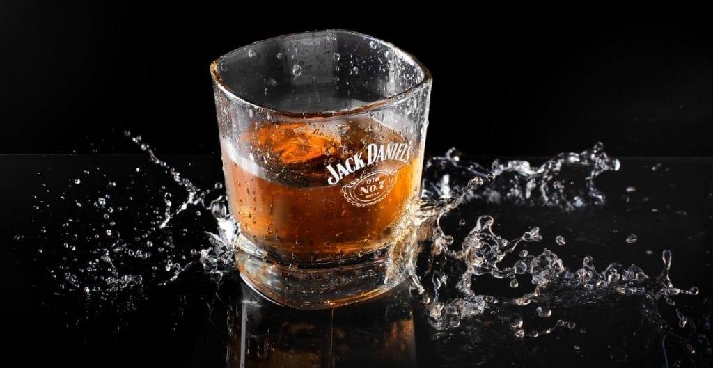 Jack Daniel's old No. 7 shot glass and splash (Canva)