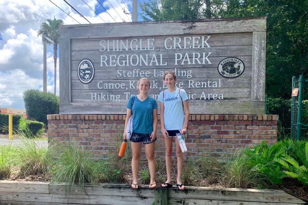 Two teen girls standing in front of Shingle Creek Regional Park sign in Kissimmee Florida