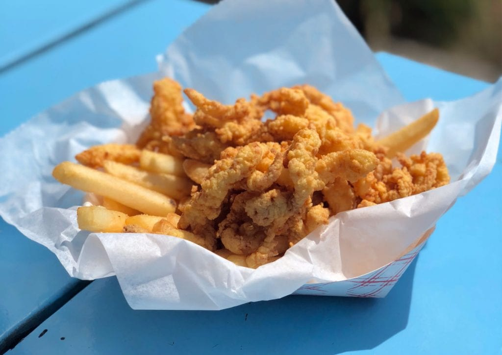 Fried clams and fries on a blue table from Bob's Clam Shack