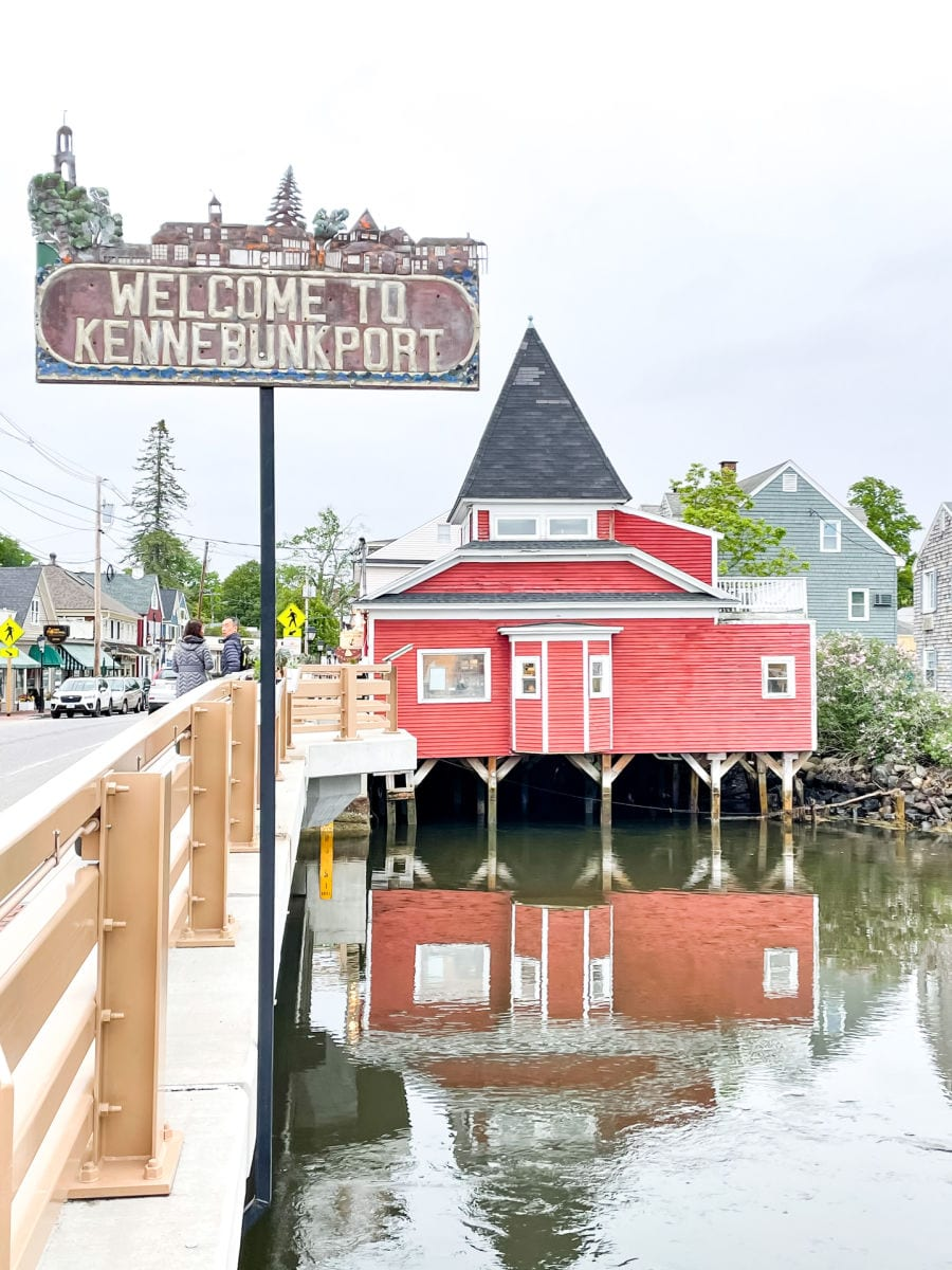 Welcome to Kennebunkport sign near bridge with red building and reflection in the water