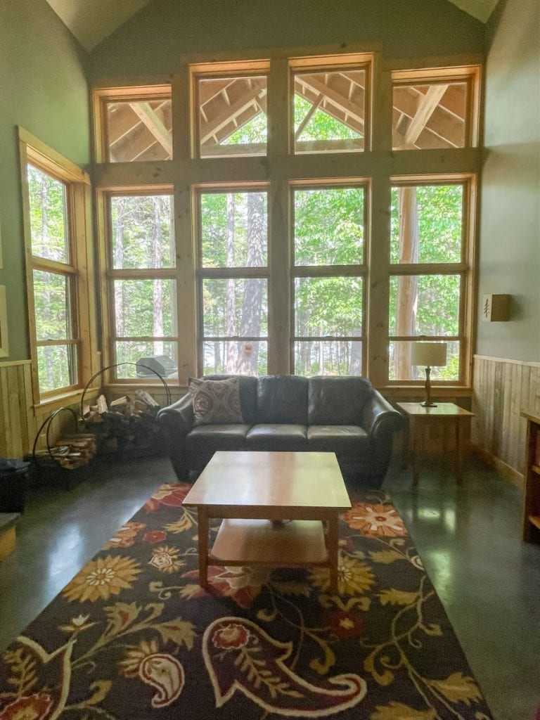Two story windows in the living room of Loon Lodge at New England Outdoor Center