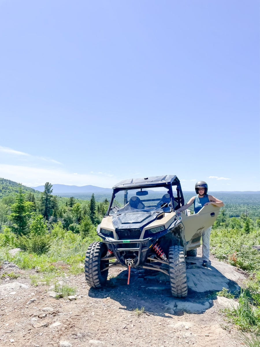Woman standing next to Polaris side by side on top of Roberts mountain